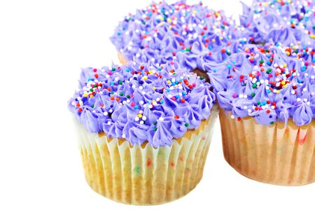 Fresh baked purple cupcakes with colorful sprinkles isolated on white with copy space. photo