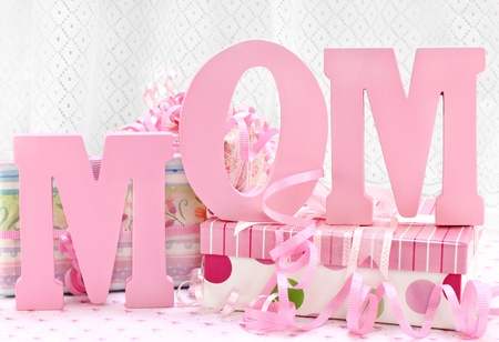 The letters MOM standing in front of pretty and feminine wrapped gifts.  A white lace curtain in the background has room for copy space. Stock Photo - 9338032