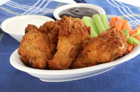 Delicious chicken wings on a plate with celery and carrots.  Sides include blue cheese and barbeque dips.