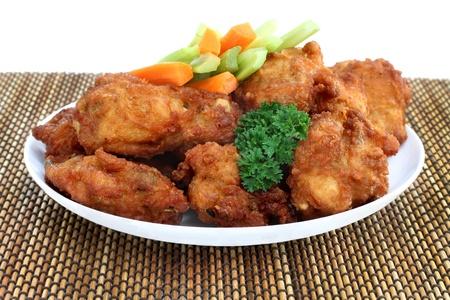 alitas de pollo: Un plato lleno de alas de pollo fresco y n�tidas con apio y zanahoria y una guarnici�n de perejil.