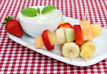 Healthy fresh fruit on kabobs with a side yogurt dip. Foto de archivo