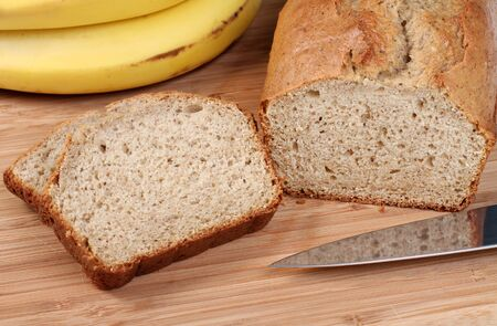 Healthy, fresh from the oven banana bread on a cutting board.  Two slices to the side withbananas in the background.