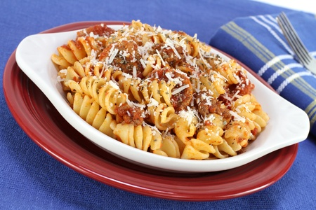 Oval baking dish of baked spriral pasta with meat sauce and freshly grated parmesan cheese. photo