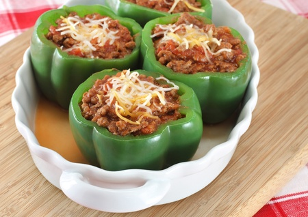Oval baking dish of stuffed green peppers with selective focus on foremost pepper. Stock Photo