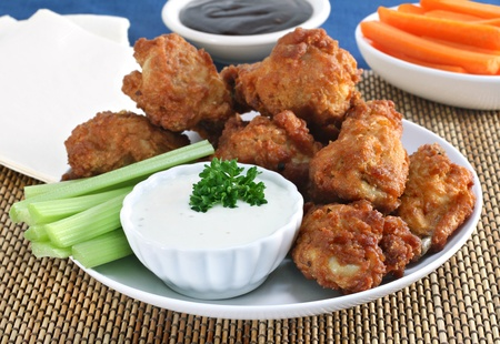 and chicken wings: Fresh delicious chicken wings with dipping sauces, celery and carrots.