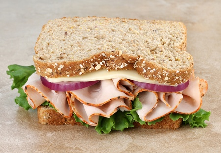 muti: Close up of a healthy turkey, cheese, onion and lettuce sandwich on whole grain bread. Stock Photo