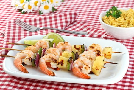 Three skewers of barbecued shrimp, peppers, onion and pineapple.  Red checked picnic tablecloth, daisies, and a side of rice. Stock Photo