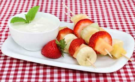 Brochetas de brochetas de fruta fresca con un lado del dip de yogur, decorado con hojas de menta.