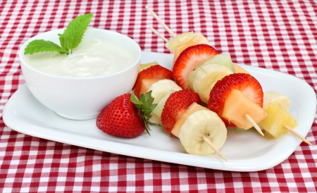 fruit: Skewers of fresh fruit kabobs with a side of yogurt dip, garnished with mint leaves. Stock Photo
