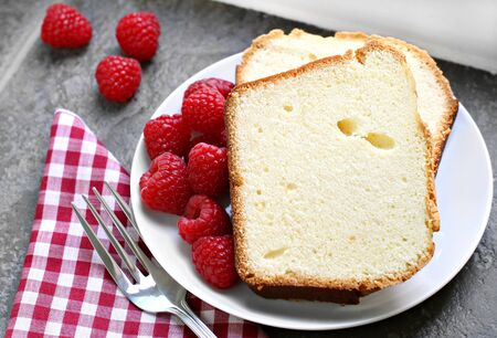 Two fresh baked slices of pound cake with raspberries on a slate windowsill. Stock fotó - 10060154