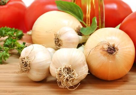 onions: Frescos del ajo jardín, cebollas, tomates y el perejil con una botella de aceite de oliva. Selectiva verduras focuson adelante. Foto de archivo
