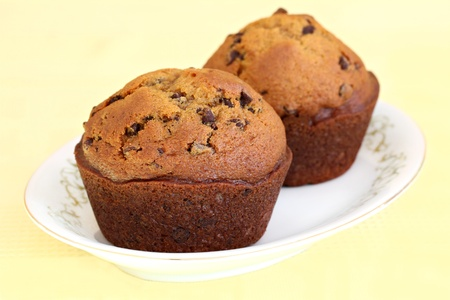 Two freshly baked pumpkin chocolate chip muffins.  Macro with selective focus. Stock Photo