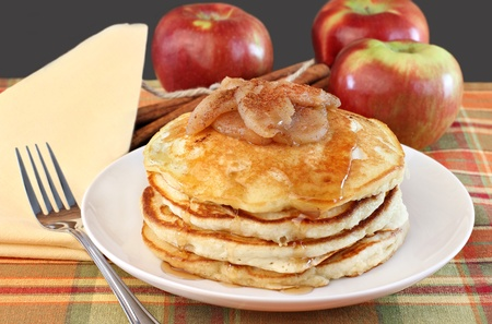 A stack of golden buttermilk pancakes with baked apple topping and syrup. Stock Photo