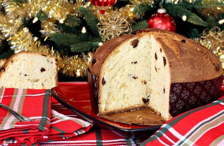 Delicious Italian panettone loaf in front of a lit Christmas tree. photo