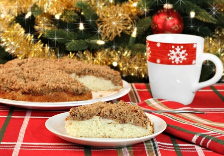 One slice of apple streusel cake in front of a sparkling Christmas tree.  Whole cake in background.