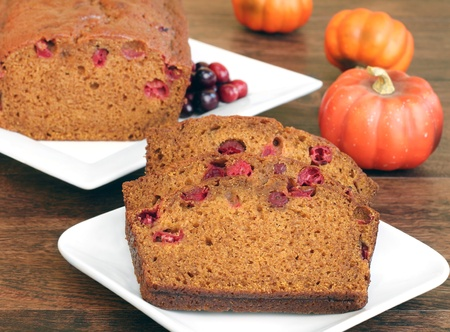 Pumpkin cranberry bread, both whole and sliced in a fall setting.  Selective focus on front slice.