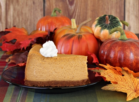 One slice of pumpkin cheesecake with whipped cream surrounding by fall decorations.