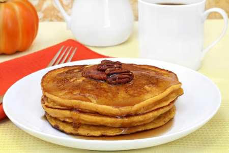 Stacked pumpkin pancakes with pecans and syrup