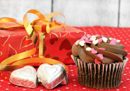 Chocolate decorated cupcake, pretty wrapped gift and candy for Valentines Day.  Close up with selectivefocus on cupcake. photo