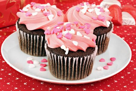 pink cake: Pink frosted and decorated chocolate cupcakes for Valentines Day.  Selective focus on front cupcake.