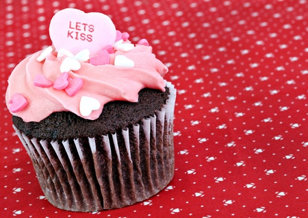 One chocolate decorated cupcake with Lets Kiss candy on top for Valentines Day.