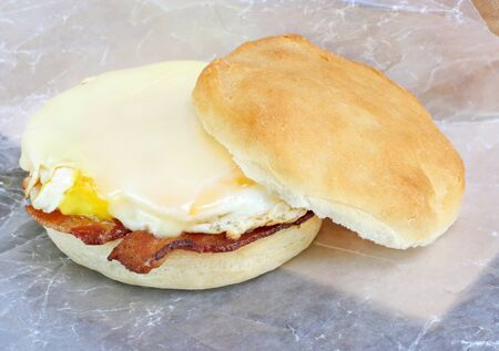 Bacon, egg and cheese sandwich on a homemade muffin.  Sandwich is on rumpled wax paper in to go fashion. Stock Photo - 12326723