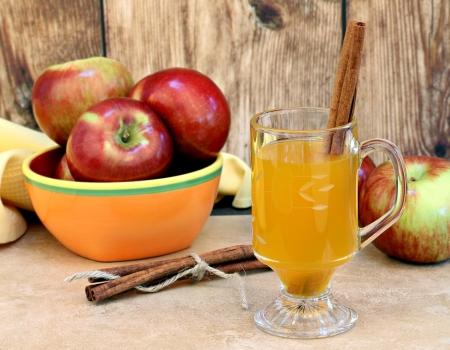 Glass mug of apple cider with cinnamon sticks.  Apples and cinnamon sticks tied with twine on the table. Foto de archivo