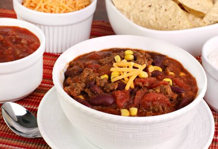 Close up of a bowl of taco soup surrounded with condiments.