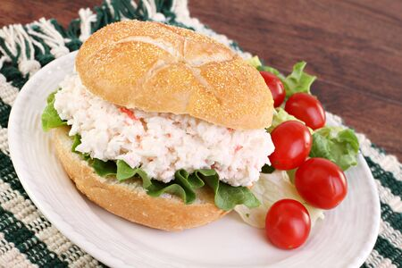 crab meat: One seafood salad sandwich on a hard roll with a side mixed greens and grape tomatos as a side.