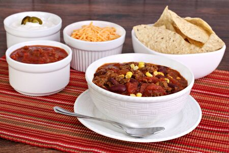 A bowl of taco soup surrounded with condiments including sour cream, salsa, tortilla chips and shredded cheddar cheese. Stock Photo
