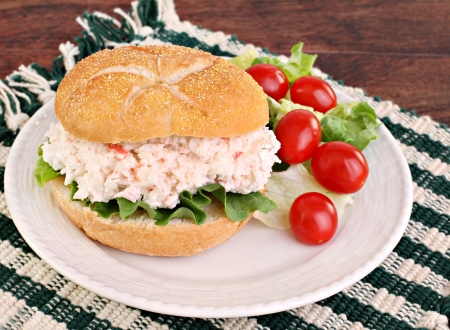 Healthy seafood salad sandwich on a hard roll with a side salad and tomatoes. Stok Fotoğraf - 12868768