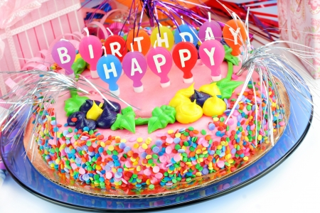 Beautiful and colorful Happy Birthday Cake surrounded with gifts and festively decorated.