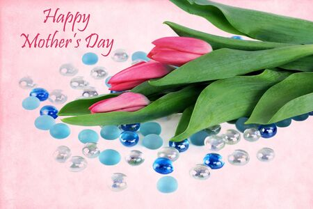 Tulips and glass beads on a vintage background with a Mothers Day wish. Stock Photo