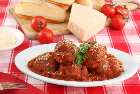 Italian meatballs in an oval dish with buns, parmesan and tomatoes in the background.