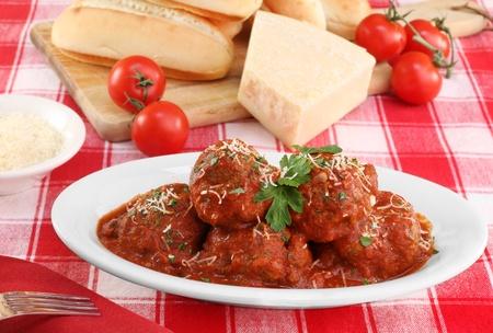 salsa de tomate: Italiana albóndigas en una fuente ovalada con bollos, queso parmesano y tomates en el fondo. Foto de archivo