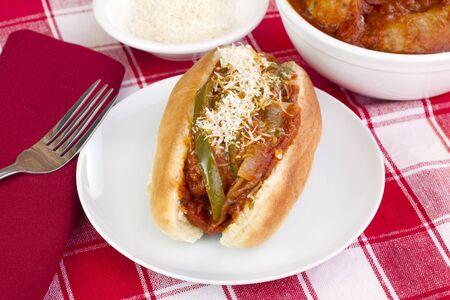Italienische Wurst-Paprika, Zwiebeln, Parmesan und Sub-Sandwich mit selektiven Fokus auf vorderen Ende. Schale mit Würstchen und Parmesan zur Seite. Standard-Bild - 13232978