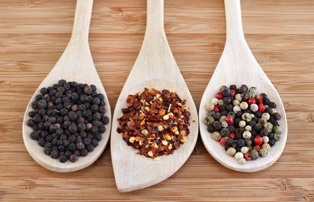 Three types of pepper on wooden spoons