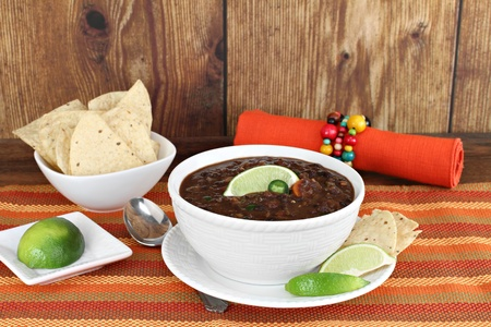 Healthy black bean mexican soup with lime and tortilla chips  photo