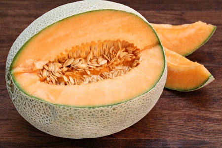 One partially cut cantaloupe, macro, with slices to the back and side.