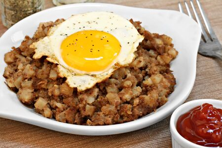 side of beef: One fried egg, sunny side up, sits on top of roast beef hash.  Ketchup to the side.
