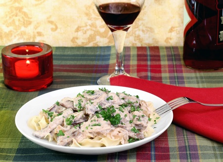 Beef stroganoff and egg noodles with wine and a lit candle in a dinner setting.