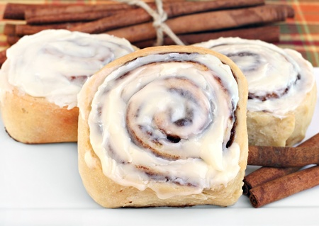 Fresly baked cinnamon buns with selective focus on standing front one.