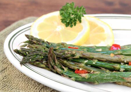 esparragos: Espárrago fresco asado con ajo y pimiento rojo asado. Macro con enfoque selectivo.