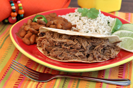 Pulled pork taco with a side of chili beans, basmati rice, and lime slices   Selective focus on meat  photo