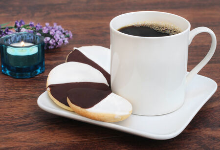 sugar cookies: Three black and white cookies with a cup of coffee  Stock Photo