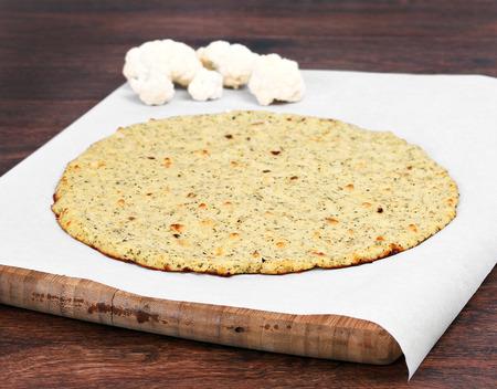 coliflor: Coliflor Llanura corteza de pizza en un pedazo de papel de pergamino en una tabla de cortar de enfoque selectivo en el borde frontal de la corteza Foto de archivo
