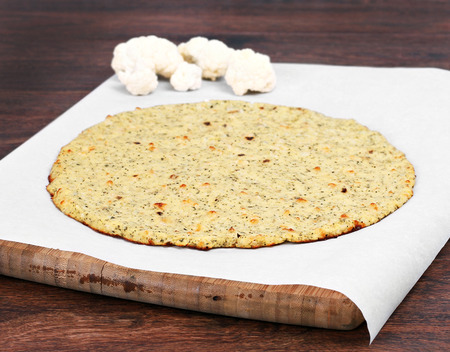 Plain cauliflower pizza crust on a piece of parchment paper on a cutting board   Selective focus on front edge of crust