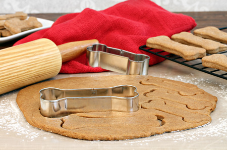 homemade cookies: Setting of a rolling pin and dog bone cookies cutters  Selective focus on cookie cutter and dough  Stock Photo