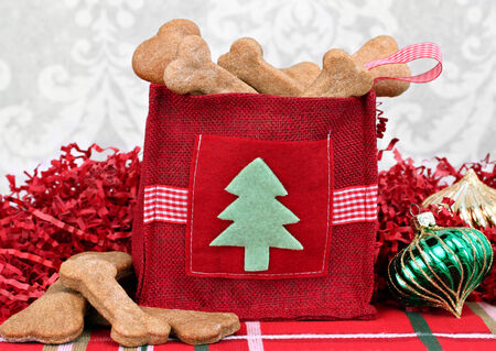 Homemade dog cookies in a decorative Christmas bag surrounded by Christmas decor  Stock Photo