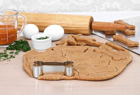 Bakken benodigdheden voor het maken van zelfgemaakte gezonde pompoen hondenkoekjes Rolling pin, deeg, pompoen, peterselie en eieren naast uitgerold hond cookies Selectieve focus op deeg